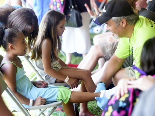 Brooklyn Williams, 5, left, of Waynesboro receives a pair of shoes Saturday from Eric Bender during Project Big Love at Mont Alto's Events Complex.