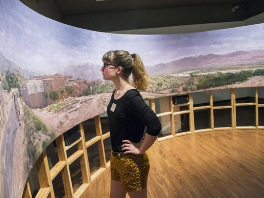 Gettysburg College student and gallery attendant Sydney Gush gets a quiet moment to examine the panoramic painting (Un)Governed Spaces after the standing room-only-crowd left the Schmucker Art Gallery on Wednesday night, the gallery's opening night for the exhibit.