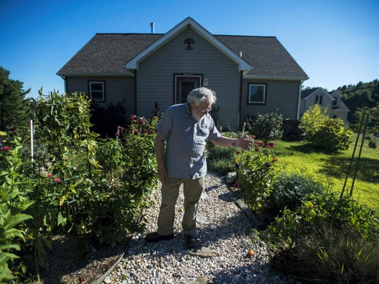 Joel Plotkin looks over the front yard garden of his home at Hundredfold Farm on Wednesday Sept. 16, 2015 in Orrtanna.  Plotkin and his wife Gretchin were some of the first residents of Hundredfold Farm, an eco-community development located on Evergreen Way. There are ten energy-efficient homes in the cohousing community, part of a community owners association, located near Seven Springs Tree Farm. Many families grow their own cooking greens and vegatables on their front lawns, and use photovoltaic and solar thermal panels to power their electricity and heat their water.