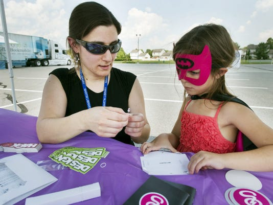 Reed Apostol, teen services librarian, left, helps Tessa DeRosa, 6, of Dover, make an origami flashlight at the Dover Area Community Library at the Girls Go Digital table.