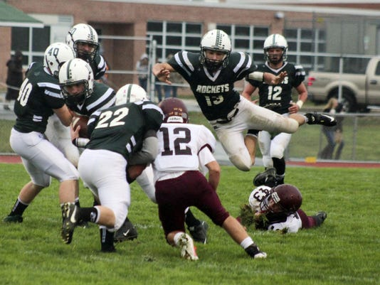 Remi Spoonhour (11) of James Buchanan slips through a hole in between blocks by Evan Stoner (22) and Kenny Gordon (40), while Big Spring's Garrett Chestnut tries to get in position. The Bulldogs won 32-6 Friday night.