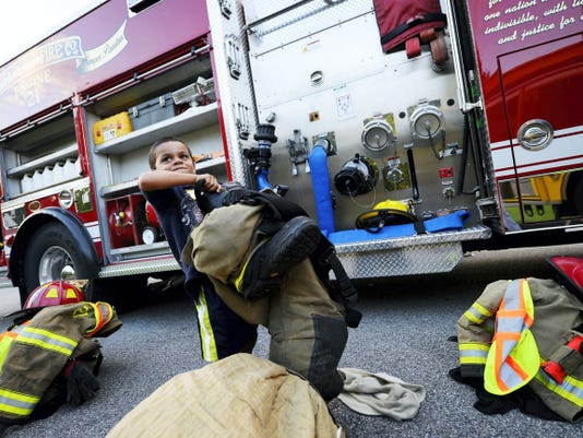 """Mark Banks, 5, of Red Lion, test his strength picking up heavy turnout gear during Community Hero Night at Grace Baptist Church in Windsor Township Wednesday. Fifth and 6th graders at the church, called """"Salt Shakers""""  invited local emergency responders to interact with church members and participate in a ceremony in the responders' honor."""
