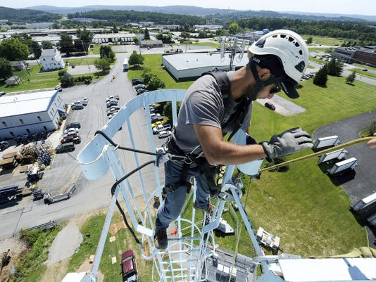 Alex Bosu, a cellphone technician with Magnus & Sons, a cellular sub contractor with AT&T, uses a pulley to bring up materials to the top of the 100-foot water tower at Farmbrook Industrial Park in Manchester Township. The entire exterior of the tower is being painted for the first time since being built in 1987, and the cell towers are being re-attached to a railing being built on top of the structure.