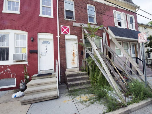 """The house at 452 E. Wallace St. is structurally unsound, according to city officials. It requires wood support beams to hold it up. The """"X"""" posted above the door warns firefighters to not enter should it catch fire. A neighbor says the building poses safety problems in her home plus problems with parking."""