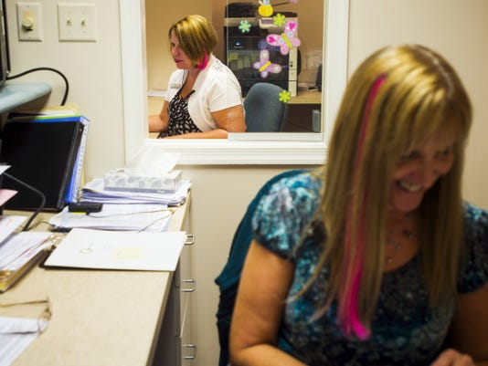 Kim Guise, background, a patient relations worker with Gettysburg Dental Associates, and treatment coordinator Jean Halvorsen, right, work at their desks Sept. 29 at Gettysburg Dental Associates on York Street in Gettysburg.  Both women were part of about 20 female employees at Gettysburg Dental Associates who dyed parts of their hair pink in support of Breast Cancer Awareness Month in October. Halvorsen and fellow employee Donna Weible are both survivors after being diagnosed with breast cancer.