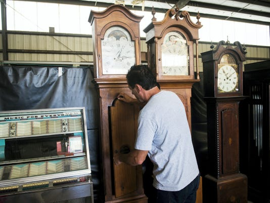 Auctioneer and Olde Tyme Auctions owner Chris Sprigle adjusts the Jessop clock's door.