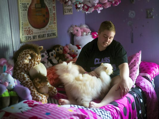 Biglerville High School graduate Brittany Arentz pets her cat, Mobey, in June at home in her Hello Kitty-decorated bedroom. Brittany's mom, Stephanie Arentz, said she wanted to get a cat to help her through chemotherapy. 'I posted on Facebook I was looking for a cat that was going to be a cancer treatment kitty,' Arentz said.