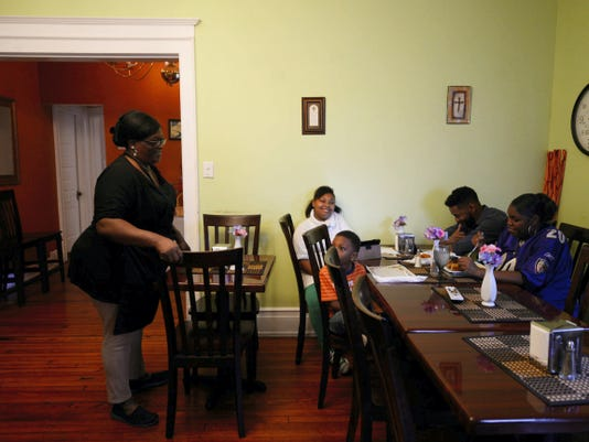 Co-owner Yolanda Thomas, left, checks on patrons Sonya Glenn, right, Zonnie Glenn, second from right, and their children Zonnie Glenn IV, 4, and Zyaire Glenn, 10, of Manchester Township at Wangs & Thangs on the 29 E. Princess St., York. Husband and wife Yolanda and Keith Thomas opened the soul food restaurant in April.