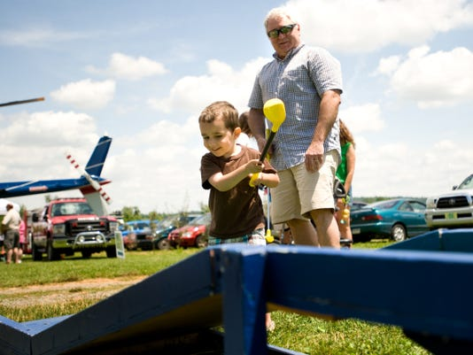 Michael Ortiz, 3, takes a swing during mini golf with his grandfather, Chris Davis, of Dillsburg, during Father's Day events at the Round Barn in 2012.