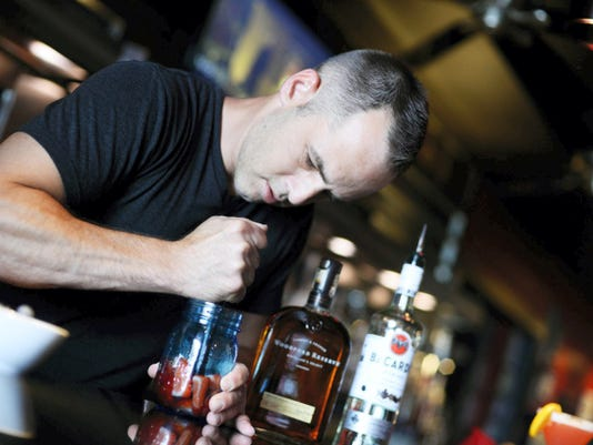 Bartender and bar manager Ryan Mapes makes a red white and blue smash, muddling strawberries with rum then adding ice, agave, club soda, sprite and blueberries for a festive holiday drink at The Left Bank in York.