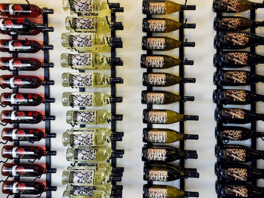 Racks of wine bottles are displayed on a wall at Allegro Winery's location in the Olde Tollgate Village shopping center in York Township.
