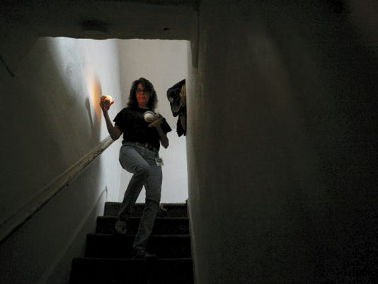"""Donna Golob carries lit sage, salt, a candle and holy water down the stairs as she performs a cleansing and blessing at a home York. Golob and other members of the Dover Paranormal Research Team will be featured on an upcoming episode of the Destination America show """"A Haunting."""" The episode will focus on one of the team's investigations in Elkton, Md."""