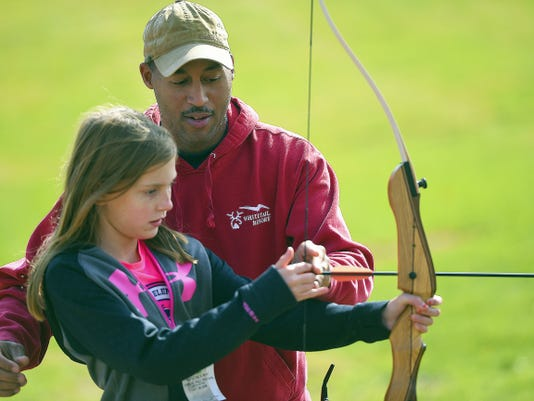 Camden Tucker, 10, of Hagerstown, Md. learns the basics of archery from Shawn Grove of Whitetail during Whitetail's 15th annual Fall Festival in Mercersburg.