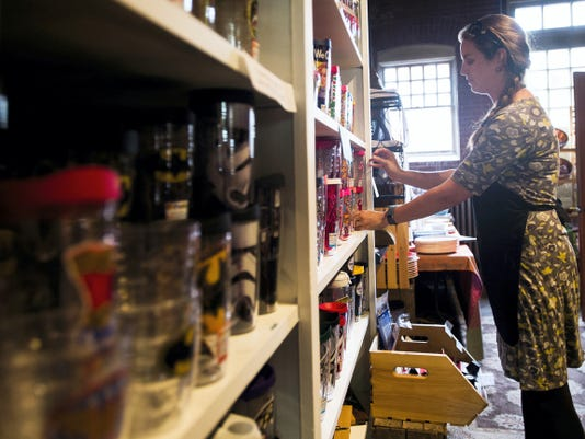 Heather Lunn, owner of the Carriage House Market, organizes a display shelf in Hanover. Lunn has owned the store behind the Sheppard Mansion for five years and focuses on selling local food and produce.