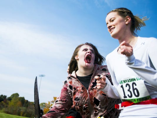 A zombie portrayed by Amy Gunzelman chases down a runner during South Western Key Club's Zombie Invasion 5K race at South Western School District.