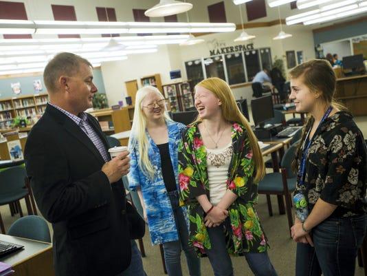 South Western High School sophomore Gwen Diener laughs while listening to Marine Corps veteran Keith Gelsinger, left, with fellow sophomore Annie Gross, right, and freshman Larkin Diener, background, Tuesday at South Western High School.