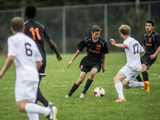 Central York's Carter Mummert, center, keeps the ball away from South Western's Jacob Wells during Monday's game at South Western. Mummert scored a second-half goal to help the Panthers earn a 4-1 victory and stay undefeated in YAIAA Division I play.