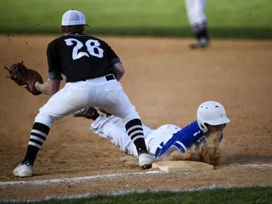 South Western's Austin Weaver waits for the ball as Spring Grove's Caleb Ruth dives back to first base safely during Wednesday's game between the Mustangs and Rockets.