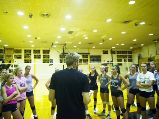 Delone Catholic volleyball players listen to instructions Monday during the first day of fall sports practice.