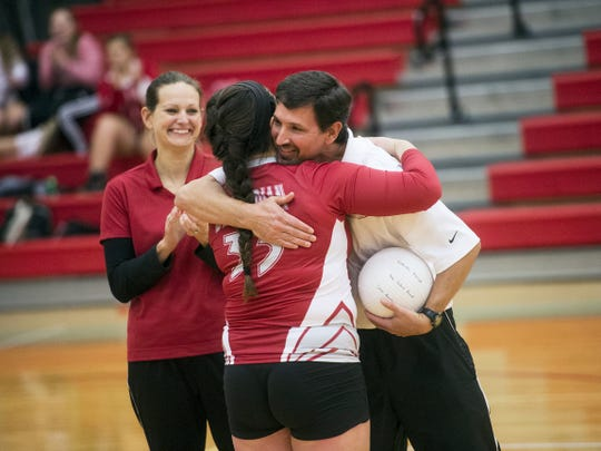 Bermudian Springs senior Gabrielle Emeigh is congratulated by coaches Mike Beachy, right, and Laura Cook during Thursday's game in which she broke the Eagles' career assists and aces records. Bermudian won, 25-18, 25-9, 25-9.