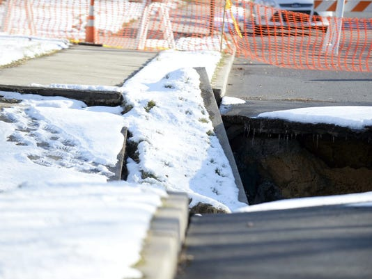 A small set of footprints in the snow leads toward a newly opened sinkhole on South Grant Street in Palmyra on Wednesday.