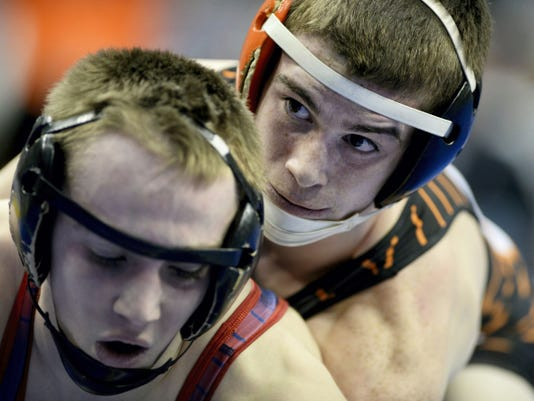 Hanover's Caleb Garland (right) battles Huntingdon's Collin Glorioso in a 120-pound first-round bout at the PIAA Class AA wrestling championships at the Giant Center in Hershey. Glorioso earned a controversial 9-7 decision, stopping the match when he was on his back after he shouted in pain.