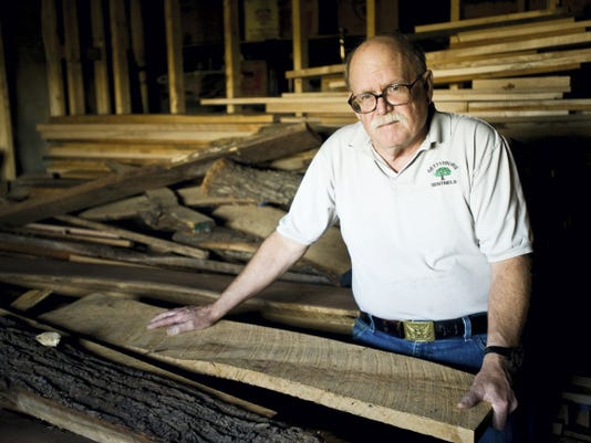 Bill Hewitt stands with witness tree remnants in the storage area of his basement, including a piece from the battlefield's wheatfield tree. 'Each piece has its own character and you have to take what the wood gives you, you can't force it. It's not like pottery,' he said.