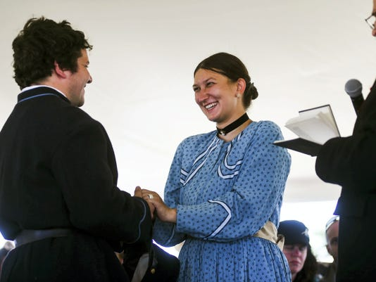 "Re-enactors Travis Roth, left, and Sara Troxell, right, take part a mock Civil War style wedding on Saturday with the Rev. Alan Farley at the 151st Battle of Gettysburg re-enactment. The two are a couple, but have only been dating about 8 months. They were ""voluntold"" for the mock ceremony, which was held in addition to a real vow renewal, at the last minute after another couple dropped out, Roth said."