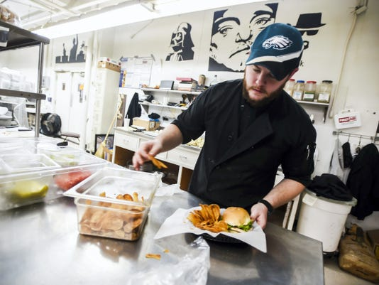 Dan Nussbaum, a cook at the Hanover Hub, prepares chips for an order Tuesday Dec. 30, 2014 during lunch time at the York Street restaurant in downtown Hanover.  Shane Dunlap - The Evening Sun