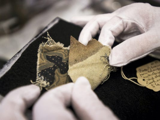 Erik Dorr, curator of the Gettysburg Museum of History on Baltimore Street, folds back a piece of upholstery to show a bloodstain. The piece of upholstery is from a couch that Adolf Hitler committed suicide on.
