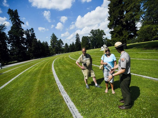 National Park Service Ranger Christopher Gwinn speaks with visitors David and Deborah Ciepluch from Milwaukee, Wisconsin at Soldier's National Cemetery in Gettysburg. Among many new programs in Gettysburg this year, visitors can attend an open house at the Abraham Brian Farmhouse on July 3 from 1 p.m. to 4.
