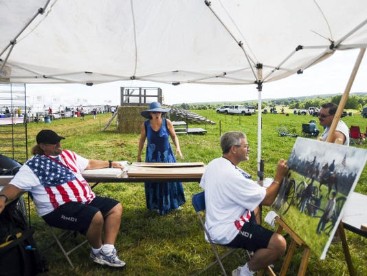 An onlooker reacts after realizing B.K. Lawes' painting is not a photograph July 4 at the 151st Battle of Gettysburg re-enactment.  Dawes, who is from Toronto, gets help from his brother, Keith Dawes, left.