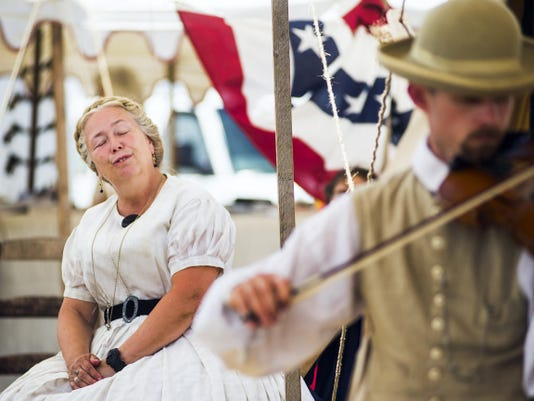 """Patty Ewers closes her eyes Sunday and sings along from her seat with the 2nd South Carolina String Band. Re-enactor Ewers said she often thinks of women of the Civil War as the first """"Rosie the Riveters,"""" a reference to a poplar home-front icon during World War II."""