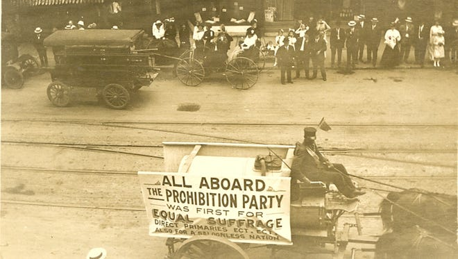The Prohibition movement had support early in Elmira. This image is from a 1913 suffrage parade along Water Street in the city. In the background is a liquor store.