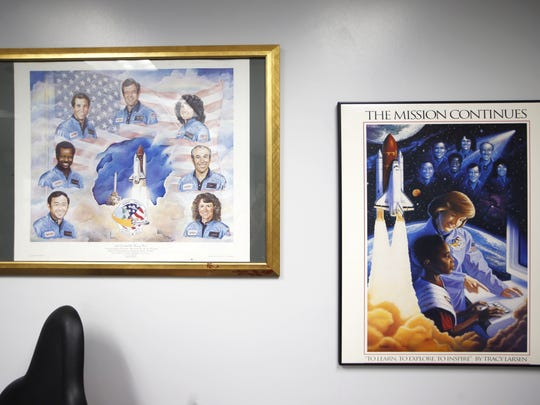 Artist renderings of the Challenger crew hang on the wall in 'Mission Control', a simulator for a flight command crew for children at the Challenger Learning Center Friday.