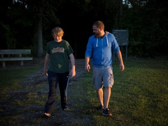 Marty Caffrey and his son, Cooper, walk together in the Madison Township Park in 2016.