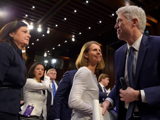 Supreme Court Justice nominee Neil Gorsuch, right, stands up during a break in his testimony on Capitol Hill in Washington, Wednesday, March 22, 2017, during his confirmation hearing before the Senate Judiciary Committee. Former Sen. Kelly Ayotte, R-N.H., left, and Gorsuch's wife Marie Louise Gorsuch, second from right, join him.