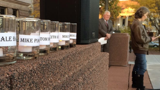 Candles bearing the names of the six men convicted in the 1992 murder of Thomas Monfils sit on a ledge outside the Brown County Courthouse in Green Bay.