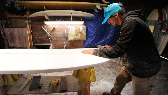 Kyle Shellhammer, owner and shaper for Eggnog Surfboards, works on a surfboard order for a client in his garage, in Coos Bay, Ore.
