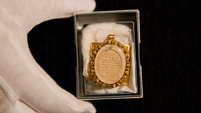 A lock of Wolfgang Amadeus Mozart's hair, contained in a 19th-century gilt locket is posed for photographs at the Sotheby's auction house in London, Tuesday, May 26, 2015.