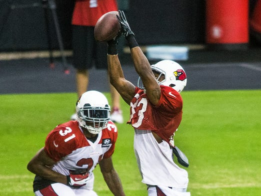 Wide receiver Walt Powell pulls in a pass as cornerback Antonio Cromarte defends at Arizona Cardinals practice, Thursday, August 21, 2014.