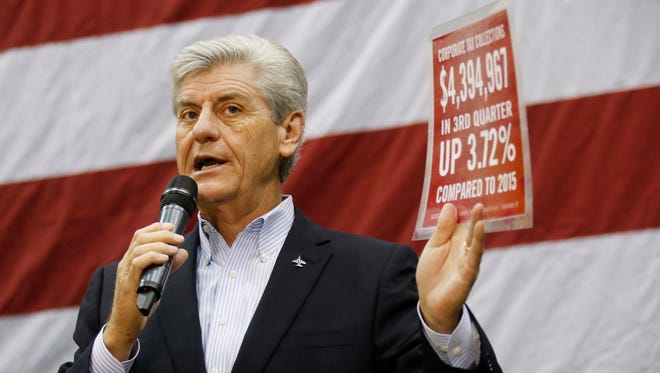 Mississippi Gov. Phil Bryant shows off some of the bullet points he uses to display the state's economic growth during the Mississippi Economic Council's annual 'Hobnob Mississippi,' in Jackson, Wednesday, Oct. 26, 2016.