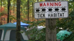 A sign warns of ticks in the area.
