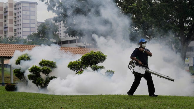 A pest control worker fumigates drains and the gardens at a local housing estate where the latest case of Zika infections were reported from on Thursday, Sept. 1, 2016, in Singapore. Indonesia is screening travelers from neighboring Singapore for the mosquito-borne Zika virus as the city-state reports a growing number of infections and its first case of a pregnant woman testing positive.