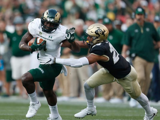 FILE - In this Friday, Sept. 1, 2017, file photo, Colorado State wide receiver Michael Gallup, left, is pulled down Colorado defensive back Isaiah Oliver in the first half of an NCAA college football game in Denver. Oliver has proven to be a standout performer in the Colorado secondary and also happens to be a rising decathlete in track and field. (AP Photo/David Zalubowski, File)