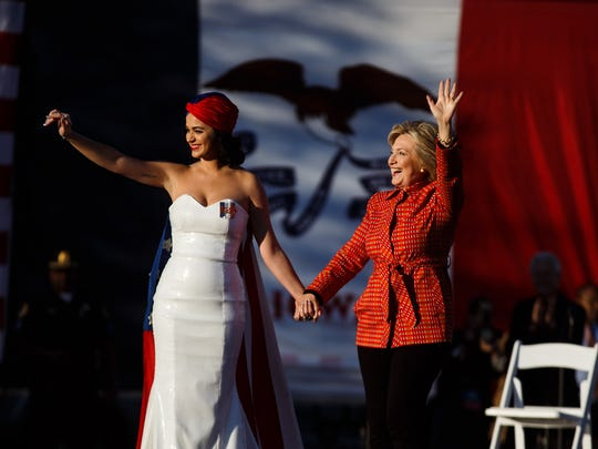 Democratic presidential candidate Hillary Clinton waves to supporters with Katy Perry during a rally before the historic Iowa Democratic Party's annual Jefferson-Jackson Dinner in Downtown Des Moines on Saturday, October 24, 2015.