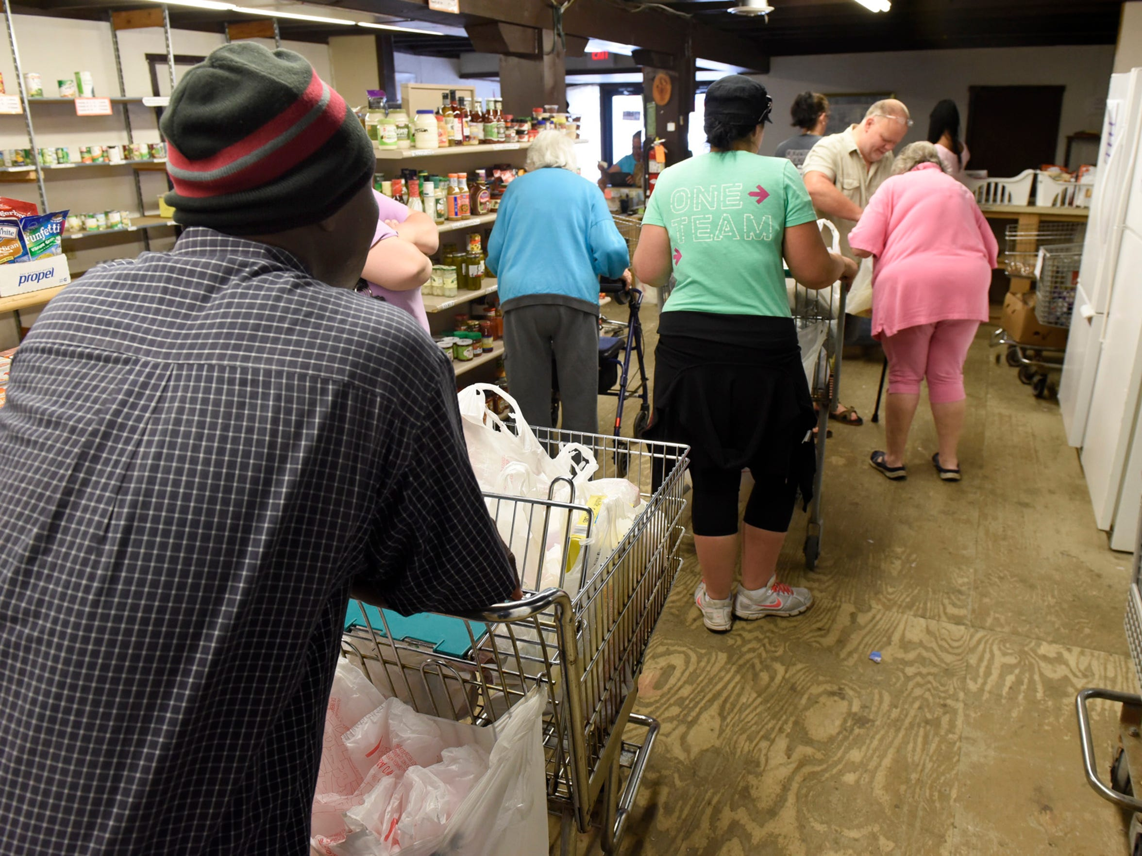 Volunteers and patrons checkout groceries Thursday,