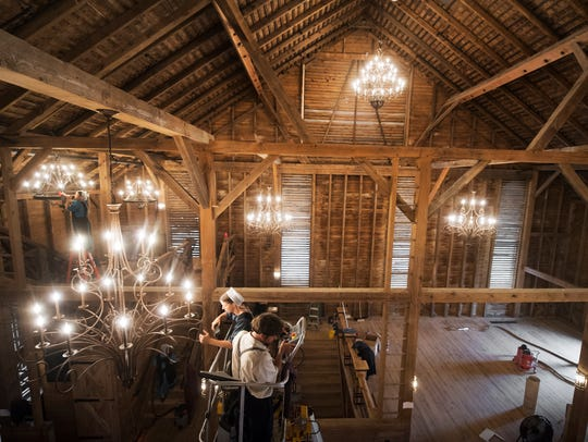 Workers clean chandeliers as work inside The Star Barn