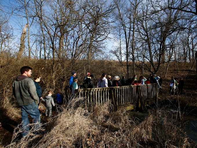 Hikers cross a bridge while taking advantage of Saturday's