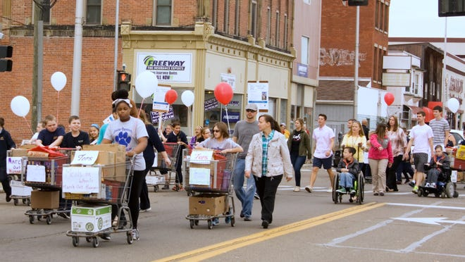 Participants march down South Main Street in Elmira from Tops Friendly Market to the Samaritan Center during Tuesday's annual March Out Hunger campaign.